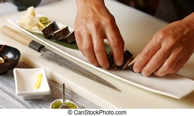 Hands put sushi on plate. Long plate with sushi rolls. Fresh...