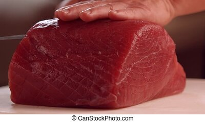 Hands with knife cutting meat.