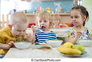 group of children eating from plates in day care centre -...
