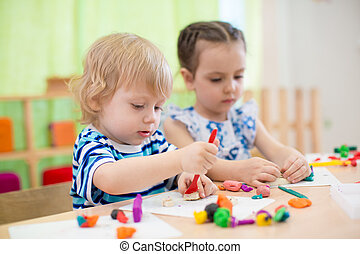 two kids doing arts and crafts in day care centre - two kids...