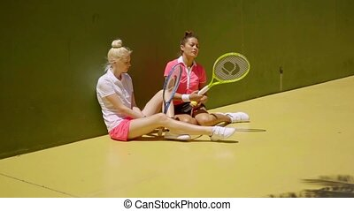 Two stylish tennis players relaxing in the sun