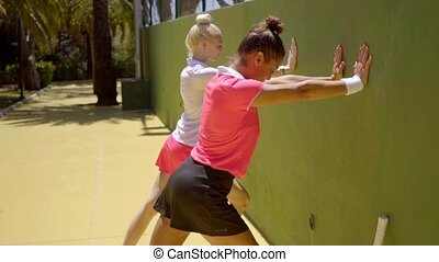 Two sporty young woman doing warming up exercises - Two fit...