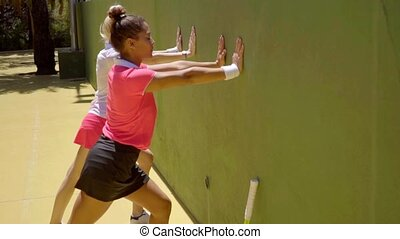 Two young woman tennis players warming up - Two attractive...