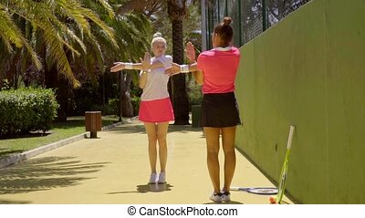 Two young attractive tennis partners warming up doing...