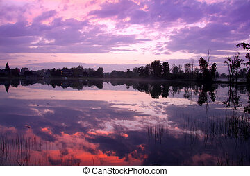Lake reflections - Colorful sun set over small lake in...