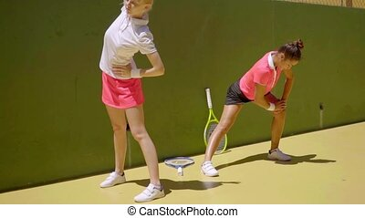 Two young women limbering up before tennis - Two young women...