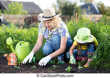 Gardening, planting - mother with daughter child plant strawberry seedlings into garden bed