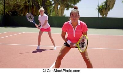Two young women playing tennis doubles standing in the ready...