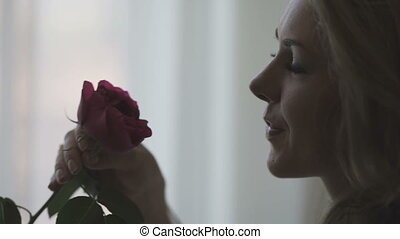 beautiful woman smelling a red rose - young beautiful woman...
