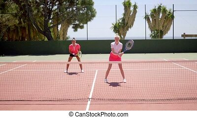 Two young woman tennis doubles players - Two attractive...