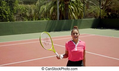 Angry young tennis player disputing a line call gesturing...