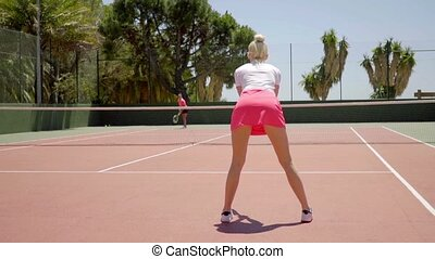 Sexy young woman playing tennis standing ready to receive...