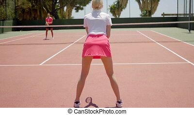 Two sporty young women playing a game of tennis outdoors on...