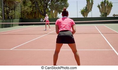 Two fit young women enjoying a game of tennis