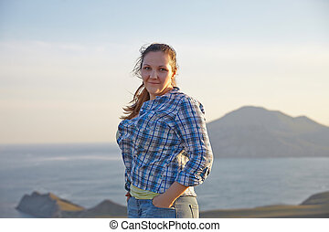 Woman looks at the edge of the cliff on the  sea bay of mountains in the background