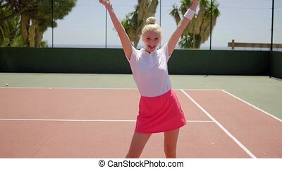 Cute woman moving with tennis racket - Single cute blond...