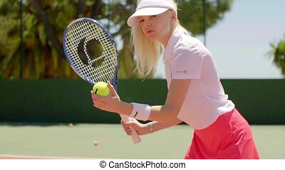 Attractive blond tennis player ready to serve - Attractive...