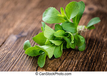 Vintage wooden table with Stevia leaves selective focus;...