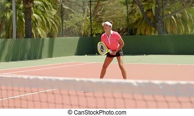 Attractive young woman enjoying a game of tennis outdoors on...