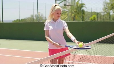Thoughtful attractive young blond tennis player with her...