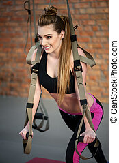 Cute fit girl is doing exercise with equipment - Portrait of...