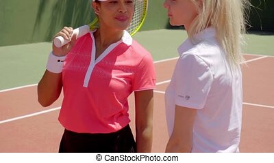 Pair of friends talking on tennis court