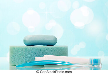 Soap, tooth paste and brush in bathroom on abstract blue -...