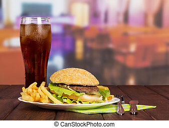 Hamburger, french fries, glass cola and cutlery on hall cafe...