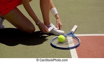 Female tennis player tying her laces - Female tennis player...
