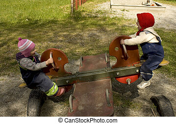 Children playing on a teeter totter in a playground