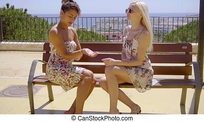 Two trendy young women sitting chatting together on a bench...