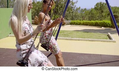 Two attractive young women chatting on swings in the park in...