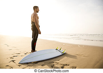 Surfing is a way of life - A surfer with his surfboard at...