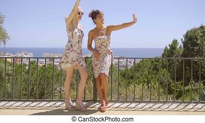 Two happy elegant young women standing waving - Two happy...