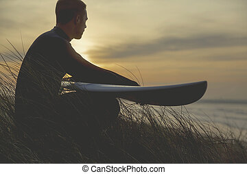 Searching for the swell - A surfer with his surfboard at the...
