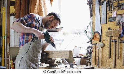 carpenter with drill drilling plank at workshop -...