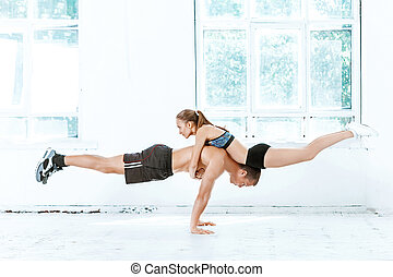 The fit woman and man doing some push ups at the gym on...