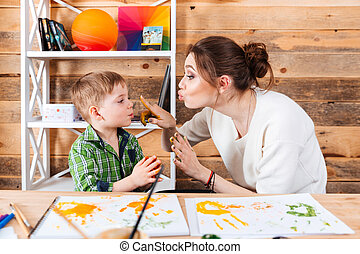 Mother touching face of son with hands painted in paints -...
