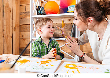 Boy and mother having fun with their painted hands - sitting...