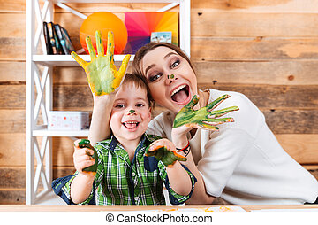 Cheerful mother and son with painted hands having fun...