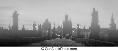 Charles Bridge in fog at sunrise, Prague, Czech Republic...