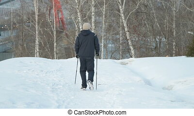 Nordic walking in winter city - Man going in for nordic...