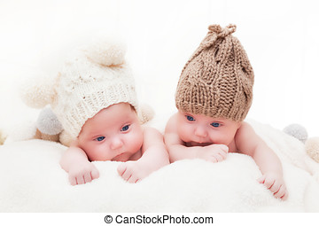 Twin sisters babies lying together wearing funny woolen...