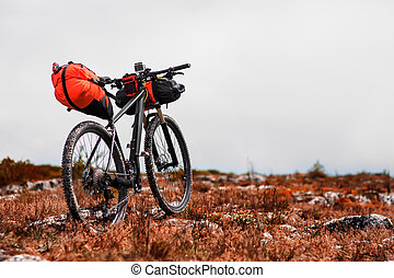 Bicycle with orange bags for travel - Mountain Bicycle...