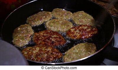 Female Hands Turning Meat Cutlets in a Frying Pan.