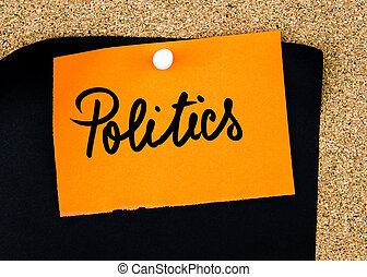 Politics written on orange paper note