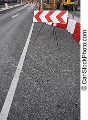 Road under construction - red stripe directional barrier...