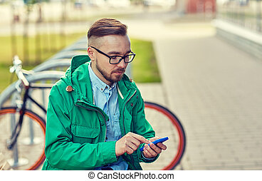 young hipster man with smartphone and byke - people, style,...