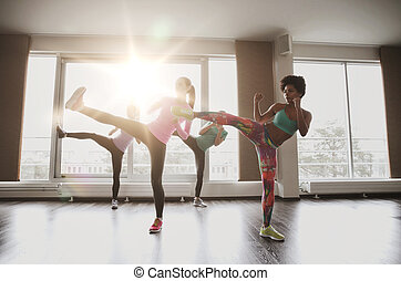 group of women working out and fighting in gym - fitness,...