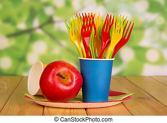 Bright disposable tableware and apple on  abstract green background.